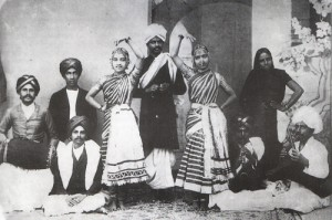 The melam or troupe of Kannuswami Nattuvanar (1864-1923) in Baroda. The nattuvanar holds the cymbals (talam) in his hands and leads the performance. Musicians traditionally stood behind the dancers. This image was taken at the turn of the century when Kannuswami Nattuvanar was invited to perform at the court of the Gaekwad princes of Baroda in northern India.